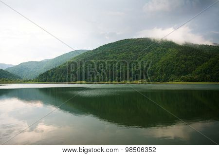 Green Forest On Mountain Lake With Mirror Reflection On The Background Of Dramatic Storm Clouds