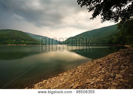 Green Forest On Mountain Lake On The Background Of Dramatic Storm Clouds