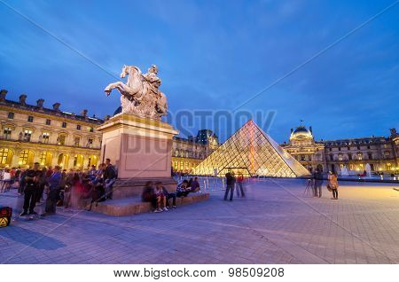 Paris, France - May 14, 2015: Tourists Visiting Louvre Museum At Dusk