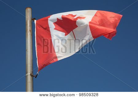 Canadian Flag Waving In The Air Over A Beautiful Blue Sky