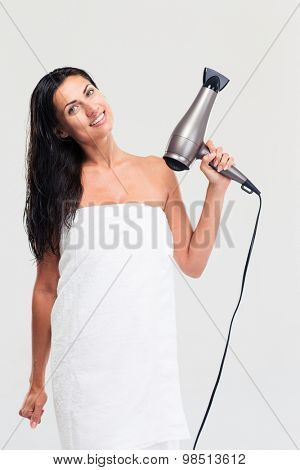 Happy young woman in towel holding hairdryer isolated on a white background. Looking at camera