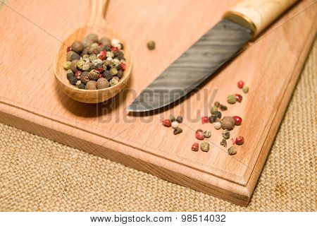 Hunting Knife, Spoon And Pepper Grains On A Wooden Surface