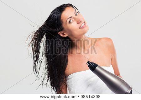 Cheerful woman in towel drying her hair isolated on a white background