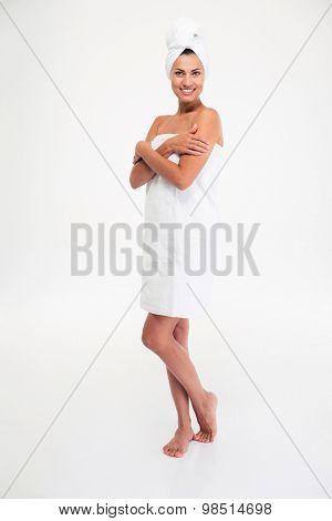 Full length portrait of a beautiful smiling woman in towel standing after bath isolated on a white background