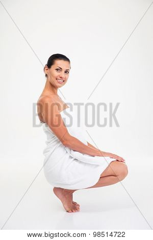 Portrait of a smiling pretty woman in towel sitting on the floor isolated on a white background
