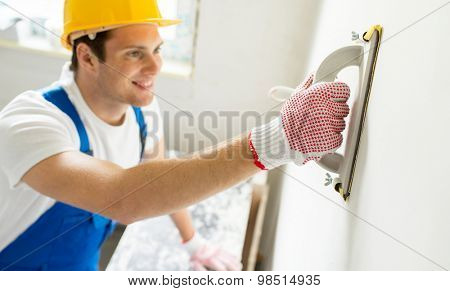 building, profession and people concept - close up of smiling builder in hardhat sanding wall indoors