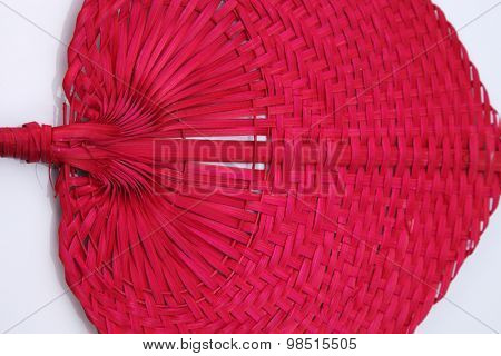 Red color native fan made from palm leaves on white background