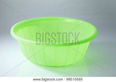 green plastic basket on a white background