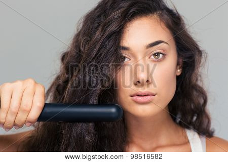 Closeup protrait of a cute woman doing hairstyle with hair straightener over gray background. Looking at camera