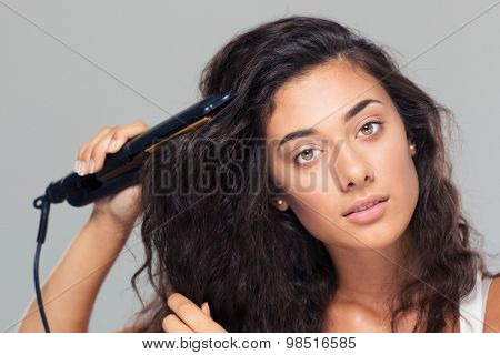 Charming woman doing hairstyle with hair straightener over gray background
