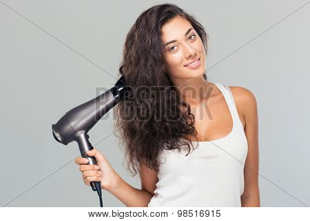 Happy beautiful woman holding hairdryer over gray background. Looking at camera