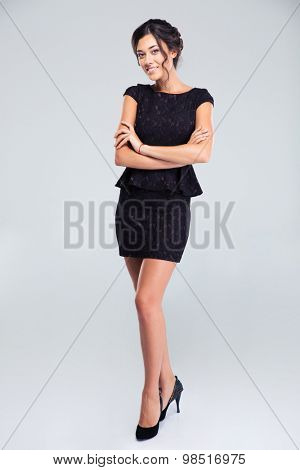 Full length portrait of a cute woman standing in fashion dress with arms folded isolated on a white background