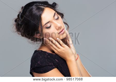 Beauty portrait of a cute woman with closed eyes on gray background