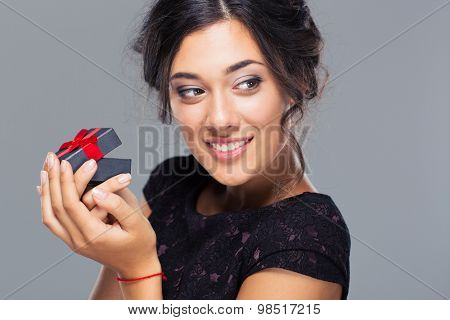 Portrait of a smiling woman holding jewelry gift box and looking away on gray background