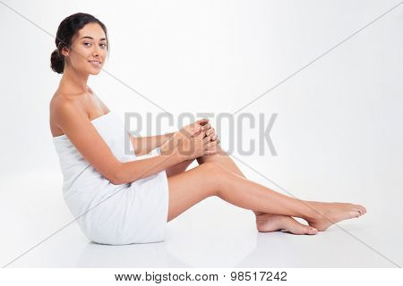 Happy attractive woman in towel sitting on the floor isolated on a white background