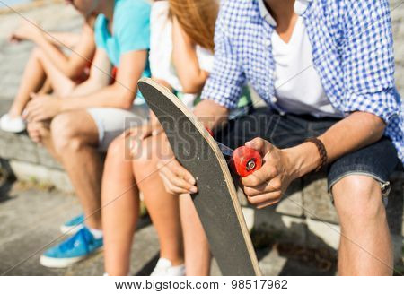 people, leisure and sport concept - close up of teenage friends with longboard talking on city street