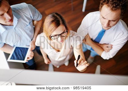 Confident businesswoman with highlighter pointing at board with two male colleagues near by