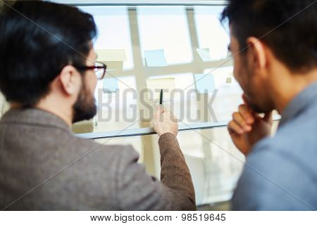 Businessman pointing at notepaper on board with colleague near by