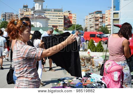 Woman Shopping Secondhand Clothes At A Flea Market.