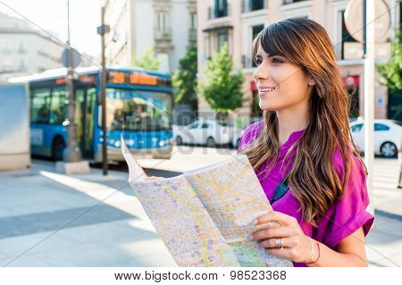 Young woman tourist holding a map in a bus station.