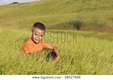Young Boy Resting Sitting In Tall Grass.