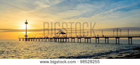 Jetty with people at sunset