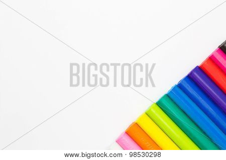 Rainbow colours plasticine play dough modeliing clay on conner of white background