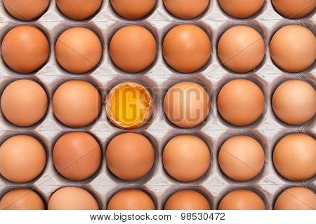 Cardboard Tray Filled With Brown Eggs, One Egg Is Broken