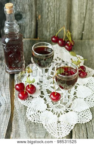 Cherry liquor in the little glasses and big bottle on the vintage napkin on the old wooden backgroun