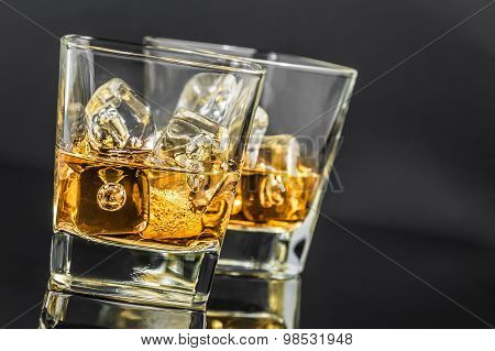 Two Glasses Of Whiskey With Ice Cubes On Dark Background