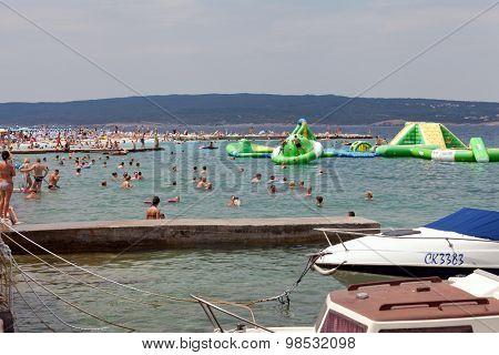 SELCE, CROATIA - JULY 24, 2015: People swimming and sunbathing on the Selce beach