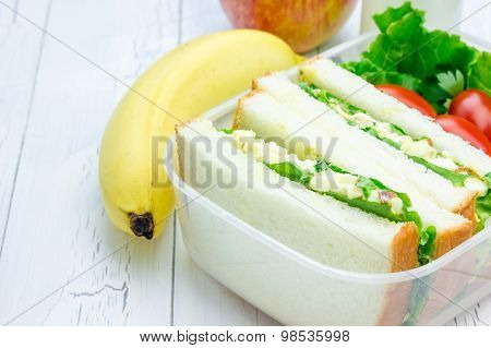 Lunch Box With Egg Salad Sandwiches, Apple, Banana And Milk