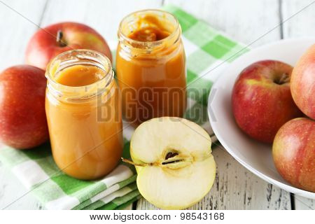 Jars Of Baby Puree With Apples On White Wooden Background