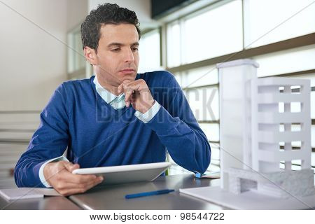 middle eastern descent businessman looking at an architecture model