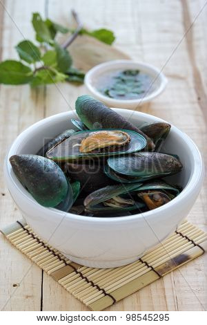 Mussels In A White Bowl On A Wooden Floor.