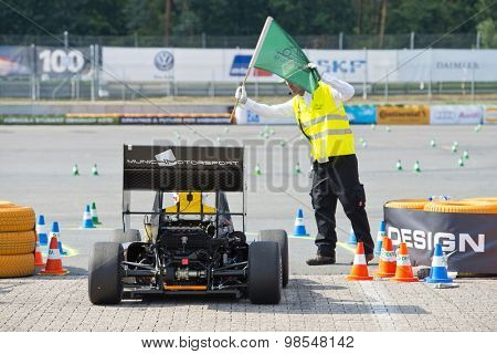 HOCKENHEIM, GERMANY - AUGUST 1, 2015: Formula Student Team Munich gets a green flag from a marshall to start the endurance race of the world championships Formula Student Germany in Hockenheim