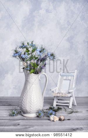 Antique jug of cut cornflowers with seashells