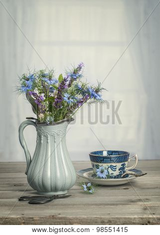Antique vase of blue cornflowers with vintage tone