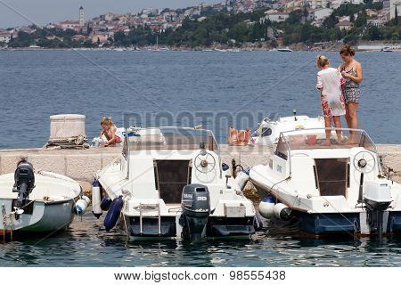 SELCE, CROATIA - JULY 24, 2015: Two women and a girl relaxing on the pier in Marina Selce