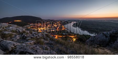View Of Lit Small City With River From The Hill At Sunset