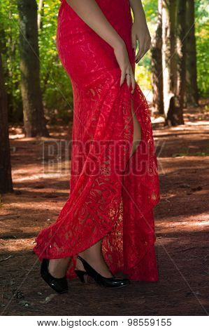 Beautiful sexy woman in a  red dress and black high heel shoes  in the forest