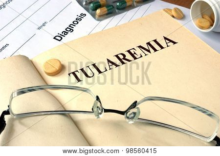 Word Tularemia  on a paper and pills.