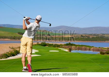 golfer hitting golf shot with club on summer vacation