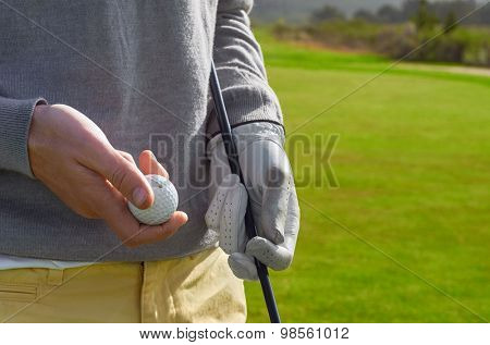 golfing man holding golf ball and club outdoors