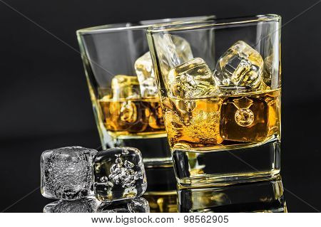 Two Glasses Of Whiskey Near Ice Cubes On Dark Background