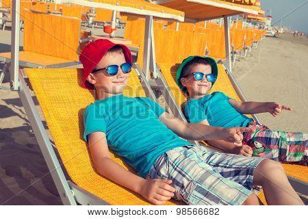 Little Boys Showing Away In Deckchair On Beach