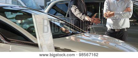 Car Dealer Presenting New Car