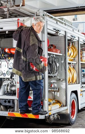 Full length portrait of confident mature fireman standing on truck at fire station