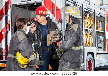 Male firefighter discussing with colleagues while holding clipboard against truck at fire station