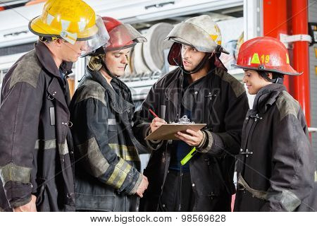 Team of firefighters discussing over clipboard while standing at fire station